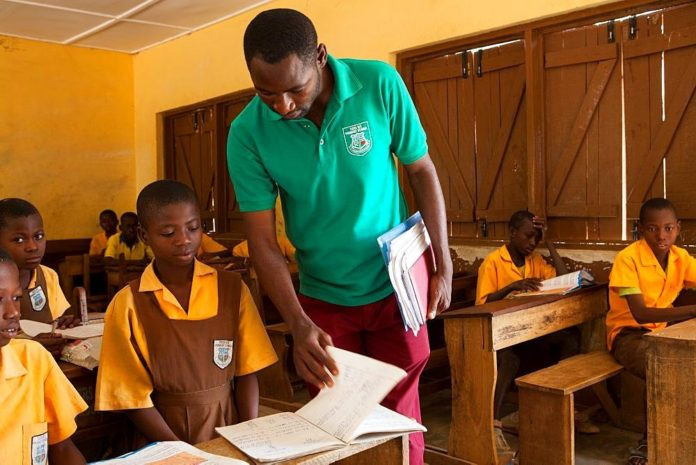 File photo: A teacher supervising the work of a pupil