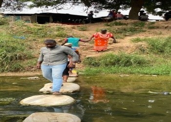 John Dumelo, crossing a stream with some constituents